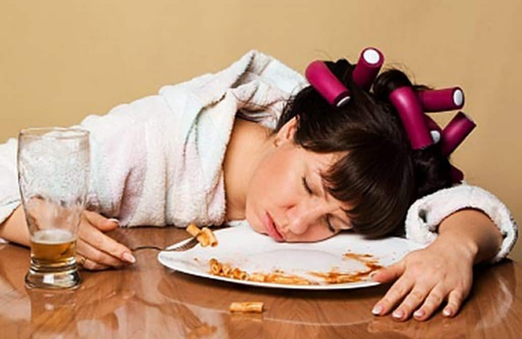 Young woman fell asleep at the table after hard eating.