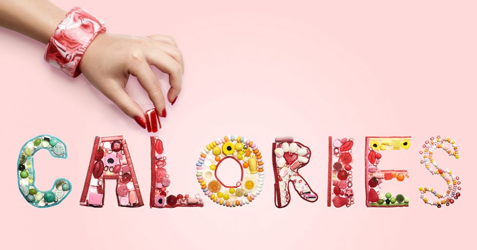 Hand arranging sweets and candy spelling Calories