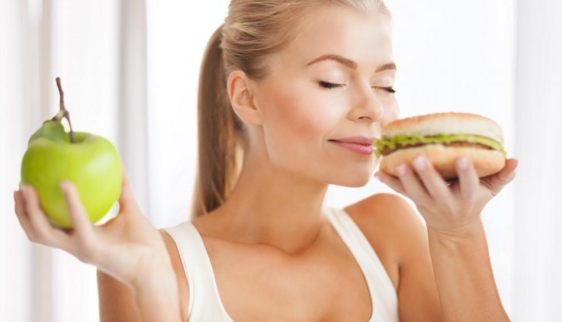 woman-in-white-shirt-smelling-burger-while-holding-apple